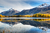 'The snowcapped Chugach Mountains and autumn foliage reflecting in Reflections Lake along the Glenn Highway in the Matanuska Susitna Valley; Alaska, United States of America'