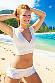 'A young woman in a two piece white outfit posing on the beach; Kauai, Hawaii, United States of America'