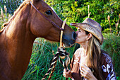 'A woman kiss the nose of a horse; Hawaii, United States of America'