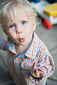 'Young boy looks quizzically up at the camera; Toronto, Ontario, Canada'