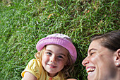 'Young girl laying on the grass with her mother laughing; Toronto, Ontario, Canada'