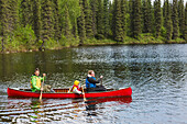 'Family in red canoe on Byers Lake with green tree covered shoreline, Denali State Park; Alaska, Alaska, United States of America'