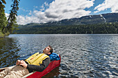 'Man reclined in canoe and resting in the sunshine on Byers Lake with forested foothills in the background, Byers lake campground, Denali State Park; Alaska, United States of America'