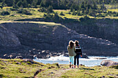 'A mother and daughter stand on a trail overlooking the Atlantic coastline at Cape Spear; St. John's, Newfoundland and Labrador, Canada'