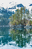 'Snow covered mountains and shoreline with trees reflected in the waters of Harrison Lagoon, Chugach National Forest; Alaska, United States of America'