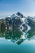 'The snow covered Chugach Mountains reflected in the waters of Barry Arm in springtime, Chugach National Forest; Alaska, United States of America'