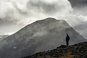'A man stands looking out from the summit of Maol Chean-dearg; Torridon, Scotland'