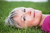 'Portrait of a woman laying on the grass; Edmonton, Alberta, Canada'