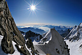 Mountaineer climbing a cornice on the ridge of Tour Ronde, Mont Maudit, Mont Blanc Group, France