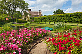 View from the rose garden across the lily pond to the manor house, Bateman's, home of the writer Rudyard Kipling, East Sussex, Great Britain