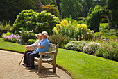 Old couple sitting on a bench in the garden, Scotney Castle, Kent, Great Britain