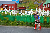 Woman wearing traditional clothing using a mobile phone passing a graveyard with wooden crosses, Nuuk, Greenland