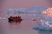 Tourists in a dinghy during excursion to Ilulissat Kangerlua Icefjord at dusk, Ilulissat, Qaasuitsup, Greenland