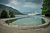 Deserted and destroyed hotel swimming pool in front of a luxurious cruiser liner in the Bay of Kotor, Adriatic coast, Montenegro, Western Balkan, Europe, Mediterrian Sea