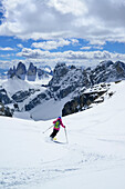 Female back-country skier downhill skiing from Hochebenkofel, Sexten Dolomites, South Tyrol, Italy