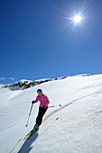 Female back-country skier downhill skiing from Corno d Angolo, Cristallo Group, Veneto, Italy