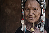 Old Akha woman in traditional clothes smoking a pipe near Kyaing Tong, Kentung, Shan State, Myanmar, Burma