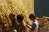 Burmese men fixing gold to the Golden Rock, Kyaiktiyo, Mon State, Myanmar
