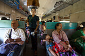 Vendor balancing food on her head and passengers in a train, Myanmar, Burma, Asia