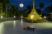 Child lying on the floor in front of a small pagoda in Lonthar village, Ngapali, most famous beach resort in Burma at the Bay of Bengal, Rakhaing State, Arakan, Myanmar, Burma