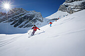 Skiers downhill skiing from mount Zugspitze, Upper Bavaria, Germany
