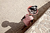 Woman carrying fish in a dish on her head, Praia, Santiago, Cape Verde
