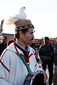 Drummer and musician with white dove on his head on the market square Djemaa el Fna in the evening, Marrakech, Morocco