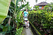Father with his two children walking along a path, baby, 3 year old boy, stroller, jungle, tropical flowers, trees, house, western family, family travel in Asia, parental leave, MR, Ubud, Bali, Indonesia