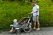 Father with his two children in front of a green wall, moss, tropical flora, baby 5 months, boy 3 years, stroller, bicycle carrier, jungle, tropical flowers, western family, Germans, family travel in Asia, parental leave, MR, Ubud, Bali, Indonesia
