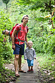 Father hiking with his son, boy 3 years old, tropical rain forest, walking, family travel in Asia, parental leave, German, European, MR, Munduk, Bali, Indonesia
