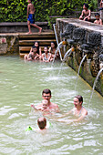 Balinese and Germans bathing, hot prings near Lovina, Air Panas, Balinese people play with baby, 5 months old, water spilling Balinese sculptures, intercultural contact, meeting local people, locals, family travel in Asia, parental leave, German, European