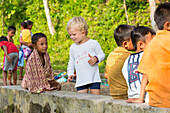 German little boy playing with Indonesian kids, children, boy 3 years old, t-shirt print please don't kiss, countryside, contact with local people, intercultural, family travel in Asia, parental leave, German, European, MR, Tetebatu, Lombok, Indonesia