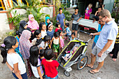 Indonesian villagers looking at little German baby, 5 months old, stroller, father, women and kids, children, Islam, head scarf, head rag, countryside, village, contact with local people, intercultural, family travel in Asia, parental leave, German, Europ