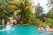 Family in a swimming pool, grandfather throwing little boy in the air, diving, mother, grandmothe,r baby, grandchildren, splashing water, holiday resort, tropical island, family travel in Asia, parental leave, German, European, MR, Sidemen, Bali, Indonesi
