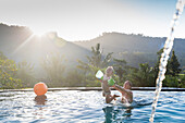 Mother and son playing in a swimming pool, mother throwing boy in the air, splashing water, water ball, sunset, infinity pool, overflow pool, boy 3 years old, palm trees, evening sun, playing, mountains, Balinese holiday resort, family travel in Asia, par