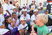 Balinese children playing with foreign boy, kids, making fun, making faces, temple ceremony, traditional dress, clothes, boy 3 years old, blond, intercultural contact, meeting local people, locals, family travel in Asia, parental leave, German, European,