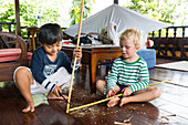 Balinese boy playing with foreign boy, German, 3 years old, blond,  knife, whittle, carving a wood stick, wooden terrace, Balinese holiday resort, hotel, family travel in Asia, parental leave, German, European, MR, Sidemen, Bali, Indonesia