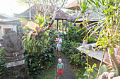 Balinese holiday resort in Ubud, father with baby on arm, 5 months, son,boy, 3 years, blond, tropical garden, sculpture Ganesha, elefant, typical Balinese architecture, hotel, evening sun, family travel in Asia, parental leave, German, European, MR, Ubud,