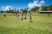 Village boys playing soccer on a field, palm trees in the distance, Sawa-i-Lau island, Yasawa Islands, Fiji, South Pacific