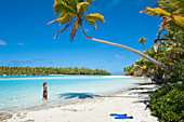 Woman strolling along the beach with palm trees at One Foot Island in Aitutaki Lagoon, Aitutaki, Cook Islands, South Pacific
