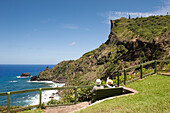 A couple sitting on a bench and admiring the coastline, Pitcairn, Pitcairn Group of Islands, British Overseas Territory, South Pacific