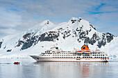 Expeditions-Kreuzfahrtschiff MS Hanseatic (Hapag-Lloyd Kreuzfahrten) vor eisbedeckter Bergkulisse, Lemaire Kanal, nahe Grahamland, Antarktis