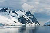 Segelboot vor eisbedeckter Bergkulisse, Lemaire Kanal, nahe Grahamland, Antarktis
