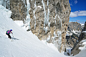 Female back-country skier skiing downhill through Val Setus, Sella Group, Dolomites, South Tyrol, Italy