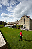 Woman in the garden of Le Cor de Chasse, food hotel by Michelin starred gourmet chef Mario Elias, manor house built in 1681 in Durbuy, Rue des Combattants 16, Weris, Wallonia, Belgium