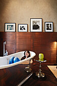 Woman in the bathtub beneath original photographs, Be Eetage Suite room no. 220, Das Stue Hotel, Drakestrasse 1, Tiergarten, Berlin, Germany
