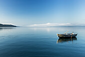 Rowing boat on Lake Starnberg, the Alps and Zugspitze in early morning fog, Berg, Upper Bavaria, Germany