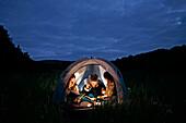 Drei junge Menschen sitzen gemeinsam in einem kleinen Zelt und lesen Bücher im Licht von Taschenlampen, Odershausen, Bad Wildungen, Nordhessen, Hessen, Deutschland, Europa