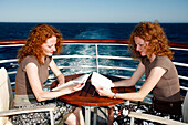 Two red-haired women (twins) sitting opposite each other reading books on the deck of cruise ship MS Europa (Hapag-Lloyd Kreuzfahrten), Pacific Ocean, near Mexico