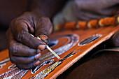 Nahaufnahme von Hand eines Aborigine Ureinwohner der mit einem altertümlichen Pinsel einen Fisch malt, Arnhem Land, Northern Territory, Australien